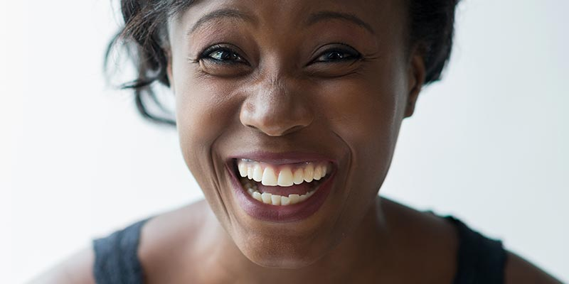 Woman with clean, white teeth looking into the camera and happily smiling