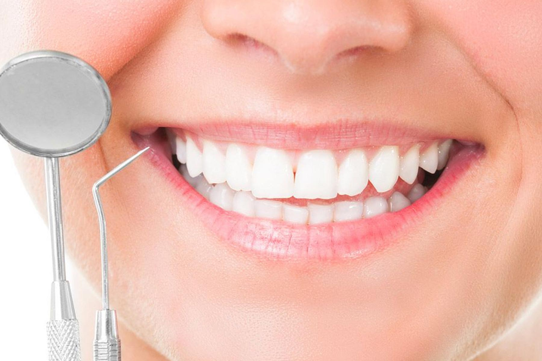Close up picture of smiling mouth with oral hygiene instruments used by dentist