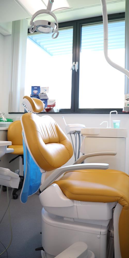 orange dental chair in clean treatment room with large window in the background
