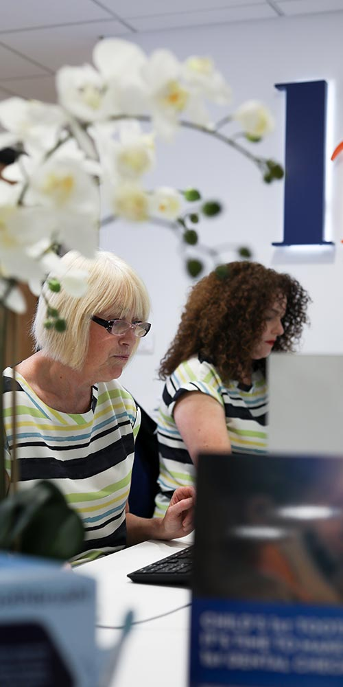 receptionists working at reception desk with white flowers in the foreground