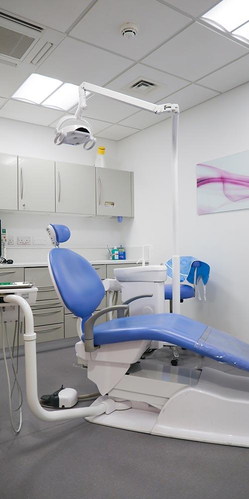 blue dental chair in clean treatment room