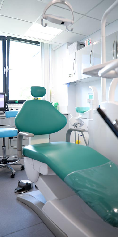 green dental chair in white and clean treatment room