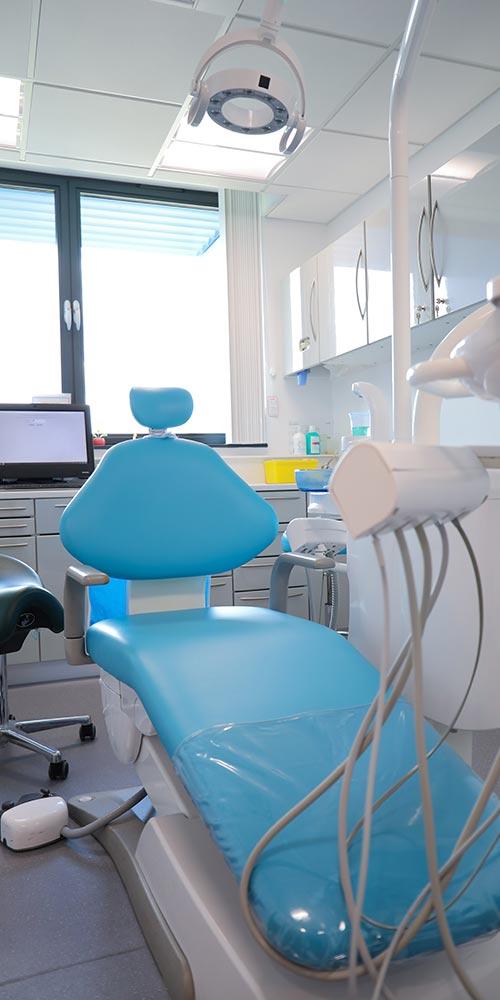 blue dental chair in white, clean treatment room