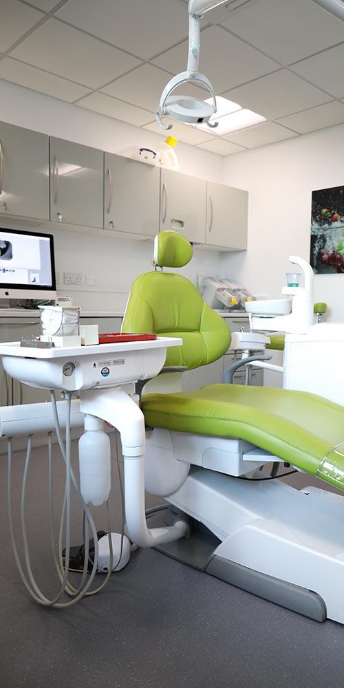 green dental chair in clean treatment room amongst dental equipment