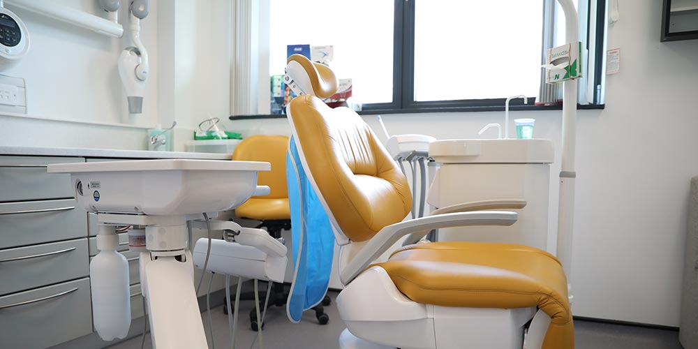 side-view of orange dental chair in clean, white treatment room