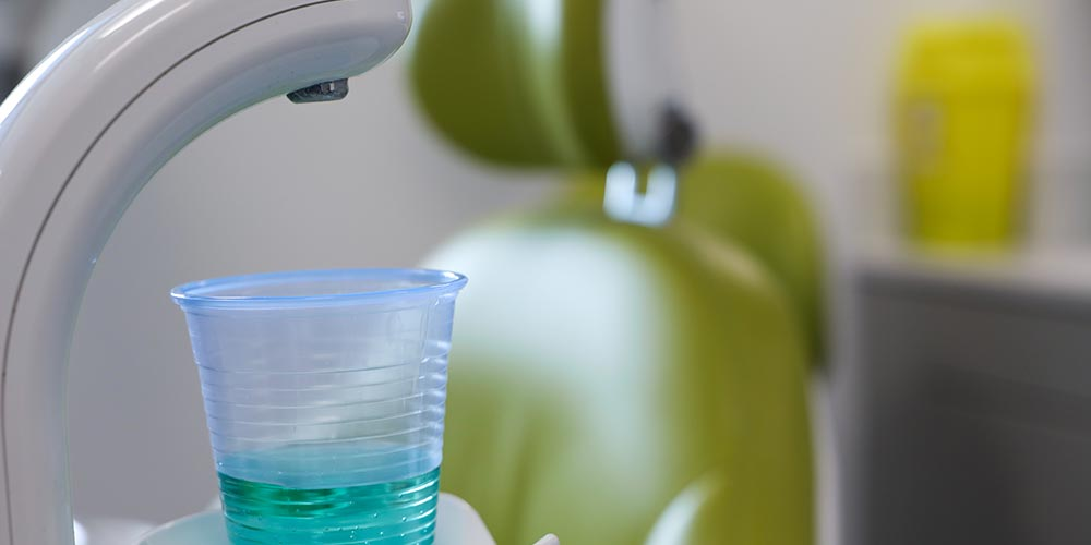 close up of disposable rinsing cup with green dental chair in the background