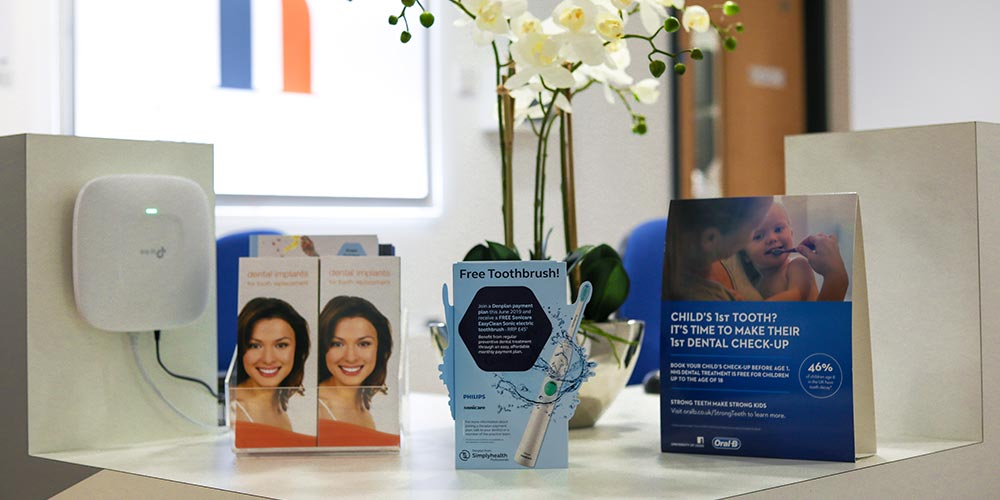 dental check by one, free toothbrush and dental implants brochures on reception desk